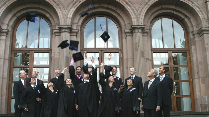 Graduates on the main building steps throw their caps in the air